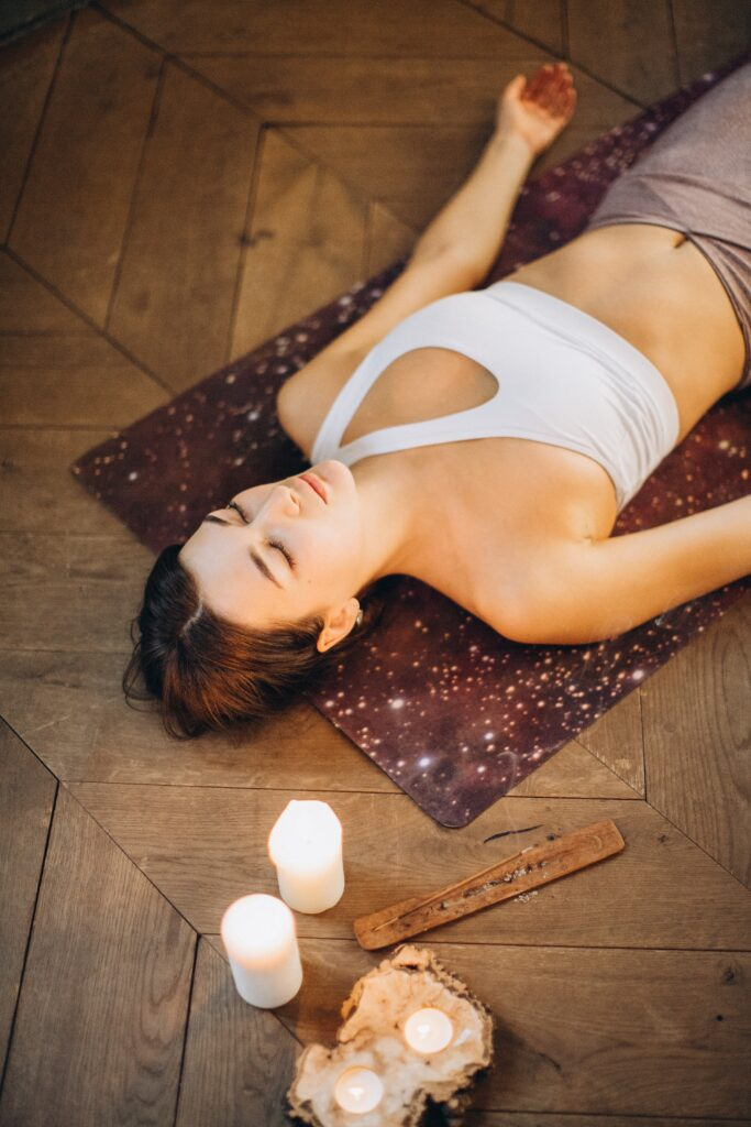Woman lying down practicing Yoga Nidra. Candles and incense are nearby